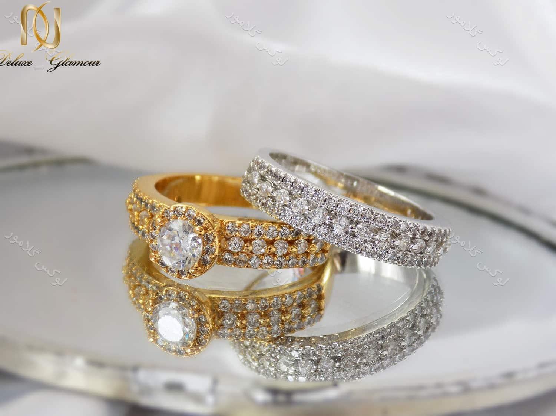 انگشتر و پشت حلقه دخترانه با المان های سواروسکی طلایی و نقره ای rg-n127 بر روی زمین