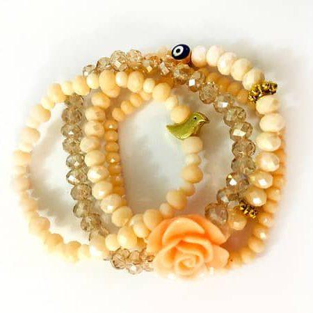 ست دستبند چهارتايي کریستالی با گل فومي و مهره چشم نظر و مرغ آمين و رنگ گلبهي روشن از نمای بالا