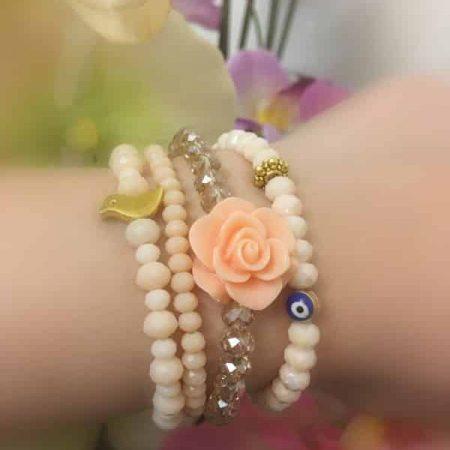 ست دستبند چهارتايي کریستالی با گل فومي و مهره چشم نظر و مرغ آمين و رنگ گلبهي روشن از نمای کنار