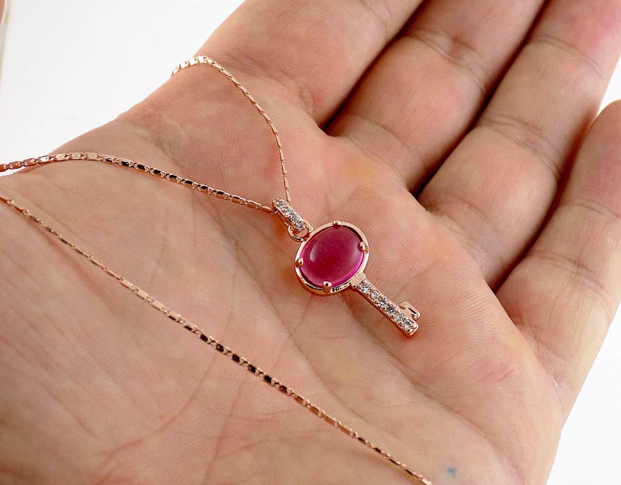 گردنبند دخترانه رزگلد طرح کلید با نگین بنفش سواروسکی اصل nw-n136 از نمای روی دست